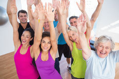 Cheerful friends with hands raised at fitness studio Stock Image