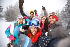 Friends with hands up on skiing. Cheerful friends with hands up on skiing stock photo