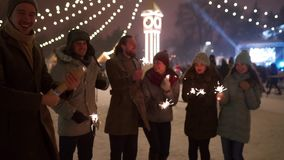 Cheerful friends have fun partying with sparklers in hands at Christmas market. People jump and dance at New Year
