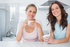 Cheerful friends having cup of coffee Royalty Free Stock Image