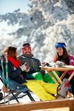 Cheerful friends having fun after skiing in resort with snow equ. Cheerful friends having fun after skiing in mountains resort with snow equipment Royalty Free Stock Photos