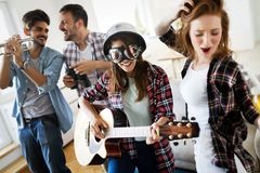 Cheerful friends having party together and playing instruments stock photography