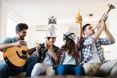 Cheerful friends having party together and playing instruments Stock Photos
