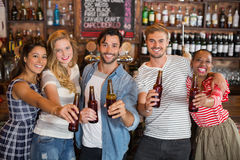 Cheerful friends holding beer bottles at pub. Portrait of cheerful friends holding beer bottles at pub Royalty Free Stock Photos