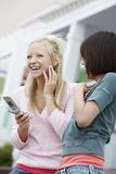 Cheerful Friends Holding Cell Phone Royalty Free Stock Image