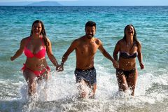 Cheerful friends holding hands and running through sea. royalty free stock photos