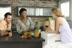 Cheerful Friends At Kitchen Counter Stock Image