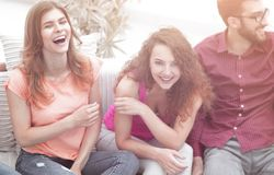 Cheerful friends laughing in the living room. stock photos