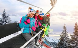 Cheerful friends are lifting on ski-lift for skiing in the mount Royalty Free Stock Images