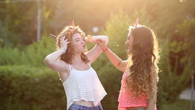 Cheerful friends with lollipops in park. Cheerful friends walking in a summer park. Girl gives to try their lollipop girlfriend. The concept of true friendship stock footage