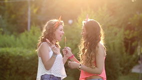 Cheerful friends with lollipops in park. Cheerful friends walking in a summer park. Girl licking lollipop from each other. The concept of true friendship stock video