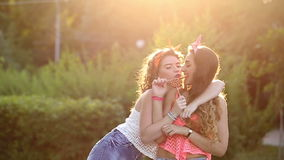 Cheerful friends with lollipops in park. Cheerful friends walking in a summer park. Girls lick lollipops. The concept of true friendship stock video