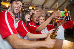 Cheerful friends looking away while holding beer bottles. In pub Royalty Free Stock Photo