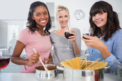 Cheerful friends making spaghetti dinner together and drinking r. Ed wine smiling at camera in kitchen Stock Image
