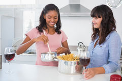 Cheerful friends making spaghetti dinner together. At home in kitchen Stock Photography