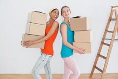 Cheerful friends moving together in a new house Royalty Free Stock Photo