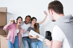 Cheerful friends in a new home fun and take photos. Royalty Free Stock Photo