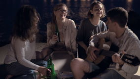 Cheerful friends at a party eating pizza ,drinking beer and playing guitar. stock video