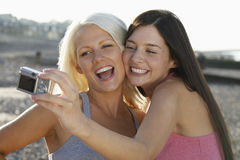 Cheerful Friends Photographing Themselves At Beach Royalty Free Stock Image
