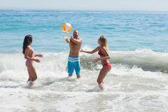 Cheerful friends playing with a beachball in the sea Royalty Free Stock Photo