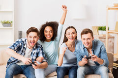 Cheerful friends playing video games. Spirit of competition. Cheerful delighted pleasant smiling friends playing video games and expressing gladness while stock photography