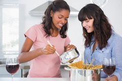 Cheerful friends preparing spaghetti dinner together Royalty Free Stock Photos