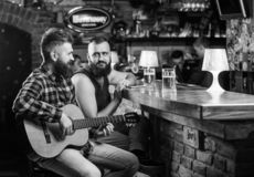 Cheerful friends relax with guitar music. Friday relaxation in bar. Friends relaxing in bar or pub. Real men leisure stock images