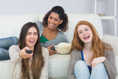 Cheerful friends with remote control and popcorn bowl at home Royalty Free Stock Photography