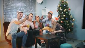 Cheerful friends in Santa hats making video call by smartphone on Christmas party. While blowing party whistle, making cheers and having fun together stock footage