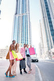 Cheerful friends shopaholics go to the store for discounts. Four Royalty Free Stock Image