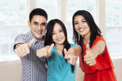 Cheerful friends showing thumbs-up. Group of happy friends giving thumbs up - isolated on white background Royalty Free Stock Photos