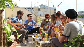 Cheerful friends sitting around table on rooftop and talking