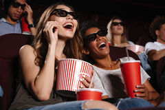 Cheerful friends sitting in cinema watch film. Picture of cheerful friends sitting in cinema watch film eating popcorn and drinking aerated sweet water royalty free stock photos