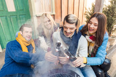 Cheerful friends sitting on porch with beer on barbeque. High angle view of cheerful friends sitting on porch with beer on barbeque Royalty Free Stock Photos