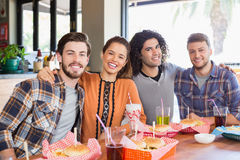Cheerful friends sitting in restaurant Royalty Free Stock Photography