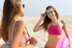Cheerful friends standing on the beach. Rise your mood. Joyful positive smiling friends standing on the beach and talking while expressing gladness stock photography