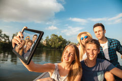 Cheerful Friends Taking Selfie On A Boat. Group Of Young Friends On A BOat Taking Selfie Using Digital Tablet stock photography