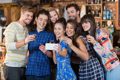 Cheerful friends taking selfie while holding short glasses. In bar Royalty Free Stock Photography