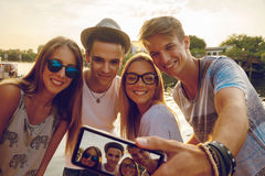 Cheerful Friends Taking Selfie Outdoors. Group Of Young Friends Near River Taking Selfie Using Digital Tablet stock photos