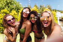 Cheerful friends taking selfie at the poolside. Group of cheerful friends taking selfie at the poolside. Beautiful women in biking taking selfie photo with soap royalty free stock images