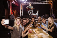 cheerful friends taking selfie while sitting at table with performer singing on stage Stock Photo