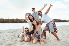 Cheerful friends taking selfie together on smartphone on beach royalty free stock photos