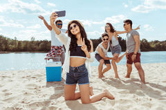 Cheerful friends taking selfie together on smartphone on beach stock image