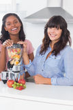 Cheerful friends about to make healthy juice Stock Photos