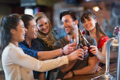 Cheerful friends toasting beer bottles. In bar Stock Photo