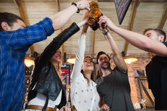 Cheerful friends toasting beer bottles and mugs. In bar Royalty Free Stock Photos