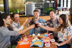 Cheerful friends toasting beer bottles in pub. Cheerful friends toasting beer bottles while sitting in pub Royalty Free Stock Photos