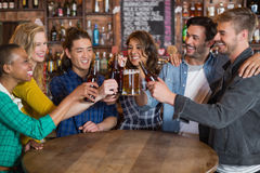 Cheerful friends toasting beer glasses and bottles. At table in pub Royalty Free Stock Photography