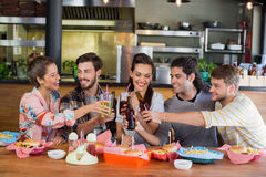 Cheerful friends toasting beer while sitting in restaurant Stock Photos