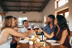 Cheerful friends toasting wine at dinner party. Cheerful friends toasting red wine at dinning table during dinner party. Group of men and women sitting around a Stock Photos